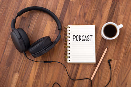 Podcast concept with headphones and coffee cup on wooden desk, top view
