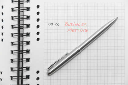 scheduled: Business meeting scheduled (with red letters) on white spiral notebook with silver pen Stock Photo