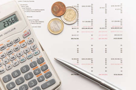 taxes budgeting: Scientific calculator, coins and elegant silver pen on financial balance sheet
