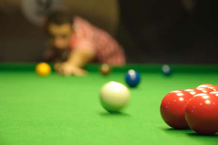 Player taking the opening shot on a snooker table photo