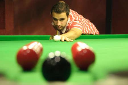 Snooker player potting an easy black ball, but through a  photo