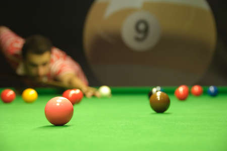 Young man playing snooker in a pub (focus on pink ball) photo
