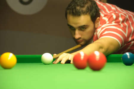 Young man concentrating before a shot (snooker) photo