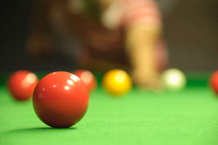 Young man playing snooker in a pub (focus on red ball) photo
