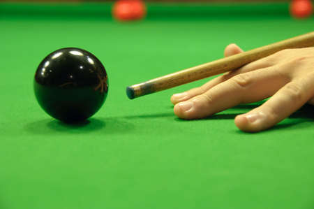 Close-up of cue striking the black snooker ball photo