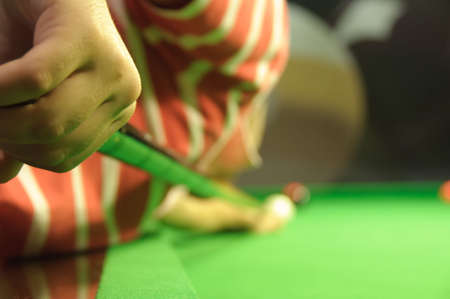 Young man playing snooker in a pub (view from behind and to the side of the player) (player is holding and swinging the cue) photo