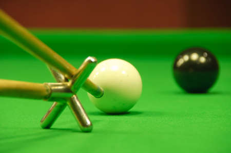 snooker table: Player striking the cue ball toward the black ball (using a rest) (view from behind)