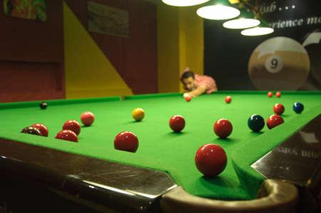 Jeune homme, jouer au snooker dans un pub (boules éparpillés sur la table) (vue depuis une poche)