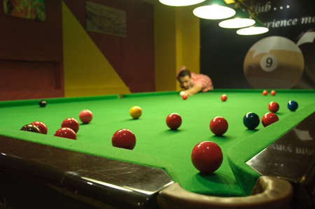 billiards tables: Young man playing snooker in a pub (balls scattered on the table) (view from a pocket)