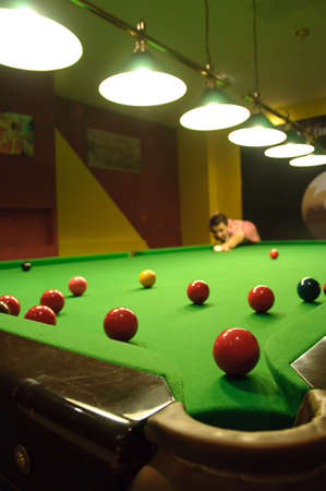 Young man playing snooker in a pub (balls scattered on the table) (view from a pocket) photo