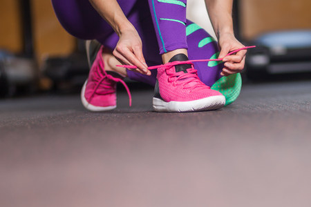 Young woman tying shoelaces in the gym Stock Photo
