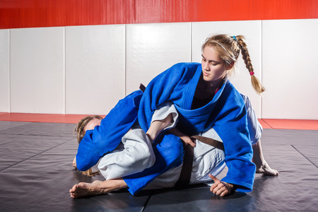 A young woman in a kimono makes a painful reception. Judo, jujitsu. Tatami, gym 스톡 콘텐츠