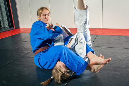 A young woman in a kimono makes a painful reception. Judo, jujitsu. Tatami, gym Stock Photo