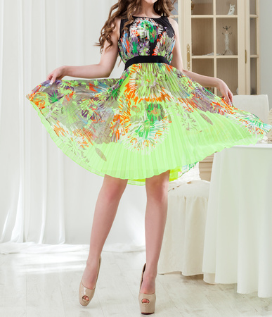 A young woman in a luxurious bright summer Lime  dress turns and raises her skirt in the studio