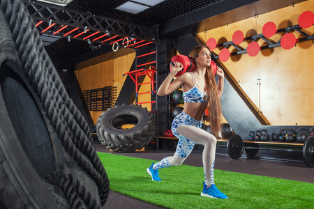 Young beautiful sporty woman doing sit-ups with a sandbag. Woman doing exercises in the gym 스톡 콘텐츠
