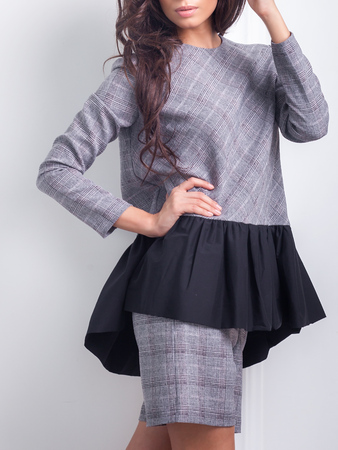 professionally: Attractive and effective brunette in a fashionable office dress with flounces professionally posing Stock Photo