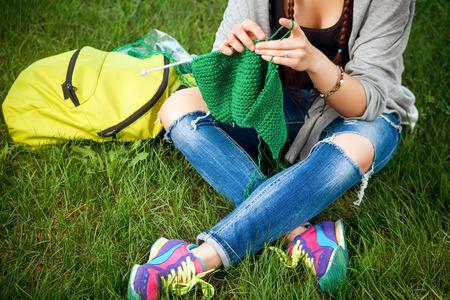 若い女性は、緑の芝生のグリーンのセーターをニットします。