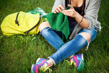 Young woman knits the green sweater on green grass .