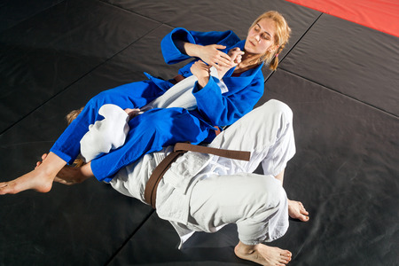 Two women are fighting on tatami.
