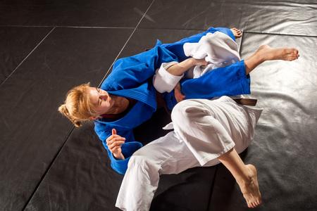 Two women are fighting on tatami. Judo, Jiu Jitsu.