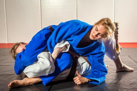 두 명의 여성이 다다미에서 싸우고 있습니다. 유도, Jiu Jitsu.