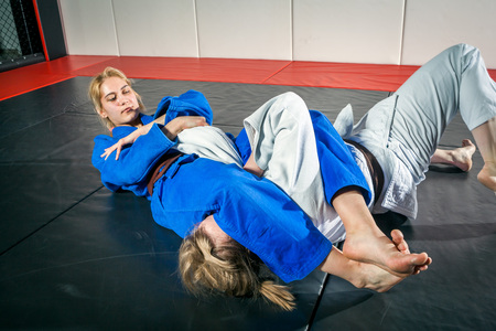 Two women are fighting on tatami. Judo, Jiu Jitsu.