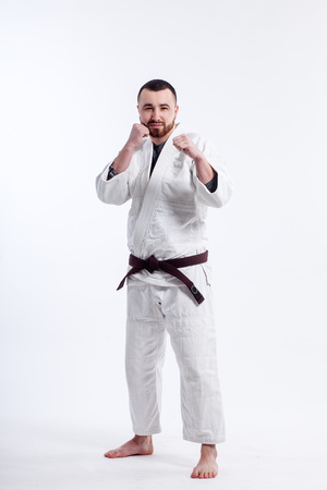 A young sporty man in a kimono. Jiu Jitsu, Judo. Coach, fighter, Wrestler. White isolated background