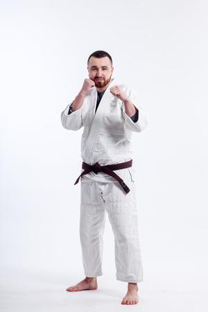 A young sporty man in a kimono. Jiu Jitsu, Judo. Coach, fighter, Wrestler. White isolated background
