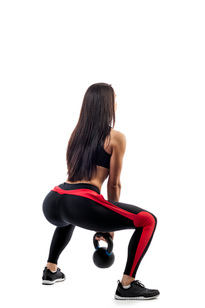 Young woman in sports clothes makes squat with weight in in full-fit position on white isolated background