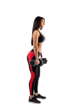 Sporty female fitness model doing an exercise on the biceps with a dumbbell on a white isolated background, two hands downstairs Stock Photo