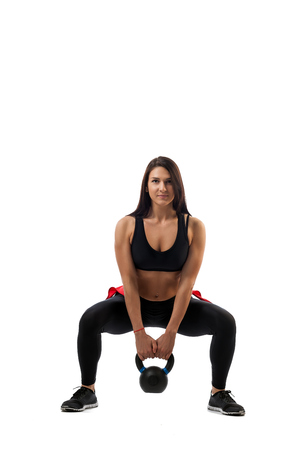 A fitness woman model makes a squat with weights on the buttocks on a white isolated background, the position of a full squat