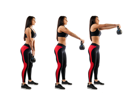 Slender brunette woman doing exhalation with weight on biceps on white isolated background, view from right side, stage of biceps exercise