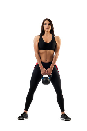 A female fitness model makes a squat with a weight on her buttocks on a white isolated background, standing position