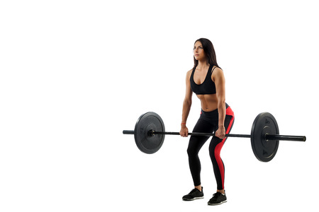 Young athletic woman doing deadlift with a barbell on a white isolated background, position of a semi-squat, legs at shoulder level