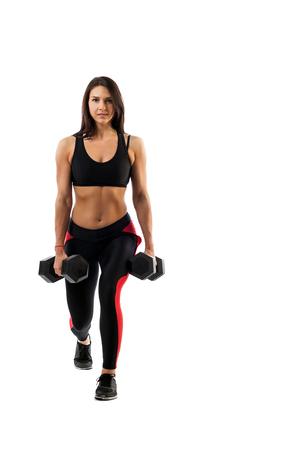 Eine sportliche Frau macht das Ausstrecken der Beine mit einer Hantel auf ihrem Bizeps, Beine in einer halben Position, Hände entlang des Torsos auf einem weißen getrennten Hintergrund