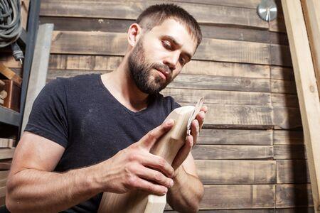 Young man builder carpenter equals polishes wooden board in workshop