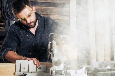Een jonge man bouwer zit aan een tafel met gereedschap en zaagt een houten bord met een cirkelzaag, chips vliegen in verschillende richtingen in de werkplaats