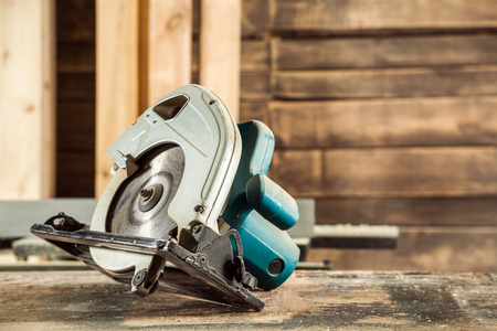 A modern green circular saw lies on a wooden table in the workshop. A close-up of a circular saw
