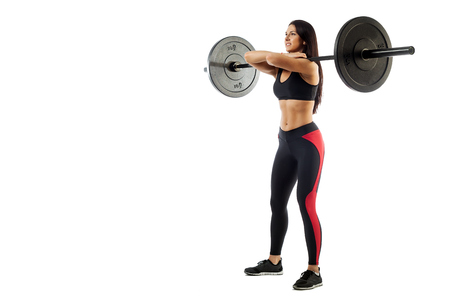 Young athletic brunette woman doing a squat with a barbell, loki in front of her, standing on white isolated background