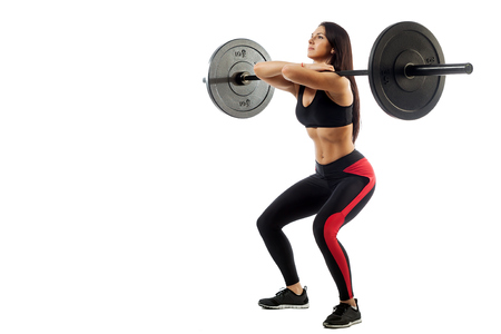 Young athletic brunette woman doing squat with a barbell, loki in front of him, position of a half-squat on a white isolated background