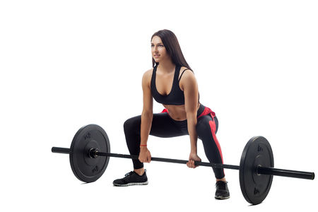 Young athletic brunette woman doing a squat with a barbell on a white isolated background, side view, legs stand wide, in a seated position, close-up