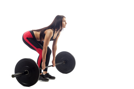 Young brunette sports woman doing deadlift with barbell on white isolated background, side view, bent position Stock Photo