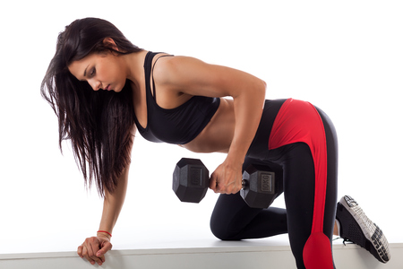 Young athletic brunette woman doing an exercise with a dumbbell on a triceps on a horizontal bench on a white isolated background Stock Photo