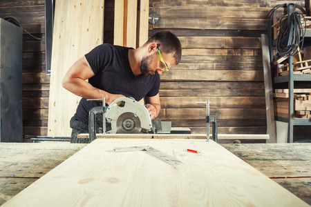 A man builder saws a board with a circular saw in the workshop