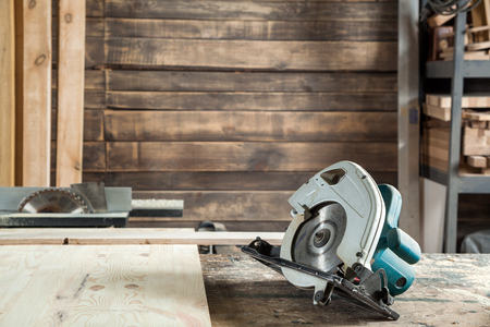 Circular saw lies on a wooden board in the workshop