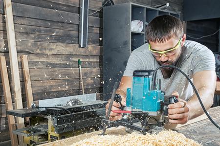 Un uomo con i capelli scuri e la barba in occhiali di sicurezza e una maglietta grigia tiene in mano una fresa e gestisce una tavola di legno in officina, nella parte posteriore della tavola ci sono molte assi di legno