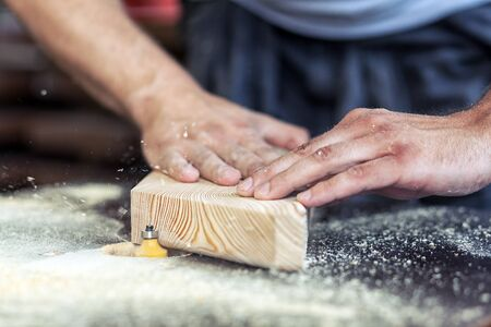 The venerable male carpenter processes the edges of the wooden product with a milling machine, close-up, the bar holds horizontally Stock Photo