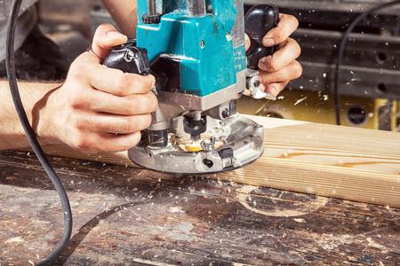 planos electricos: Close-up de cómo una moderna máquina de fresado verde trabaja en madera, sobre un fondo de madera de la mesa