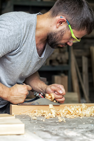 A young man with a beard and in sunglasses by profession, the carpenter holds a black jack plane in his hands and equals a wooden board, in the background a lot of wooden boards and equipment