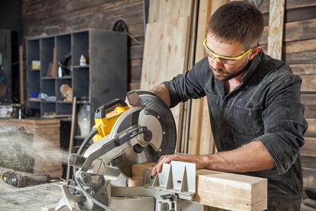 Jonge brunette man in zwarte overalls van beroep timmerman bouwer zagen met een cirkelzaag een houten plank op een houten tafel in de werkplaats